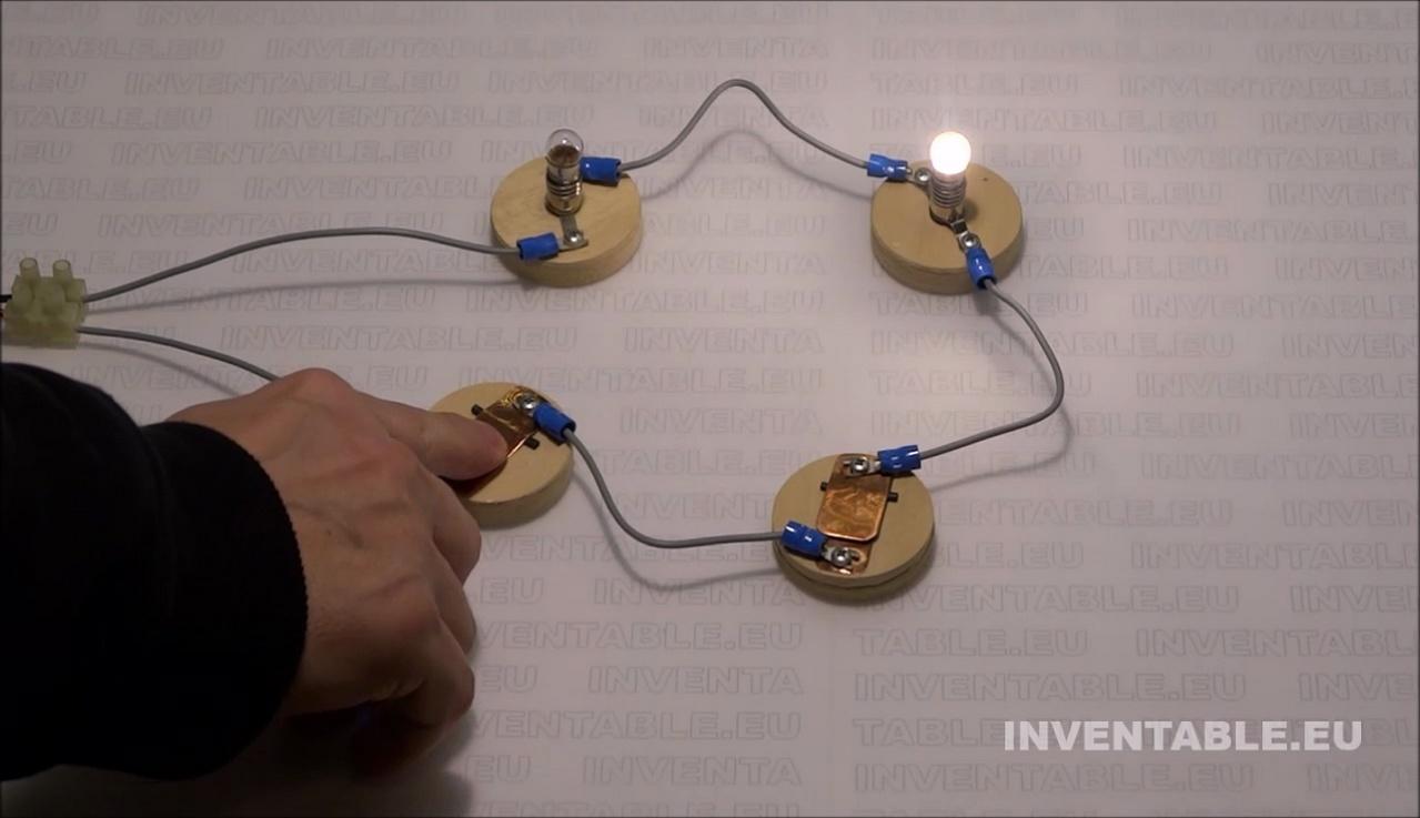 El vídeo muestra un circuito serie con dos interruptores y dos lamparitas. Por un misterioso motivo, las lámparas se encienden individualmente.